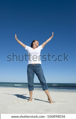 An attractive looking mature woman in her fifties is enjoying early retirement with a day on the beach, standing with her arms up, wide open ocean and clean blue sky as background and copy space. - stock photo