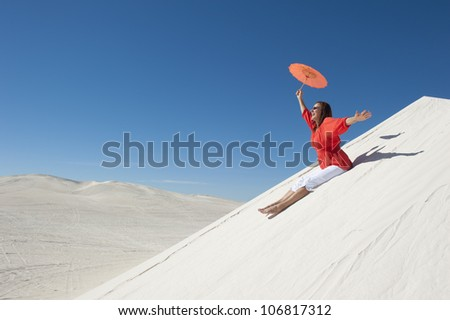 An attractive looking mature woman, wearing red blouse, sitting cheerfully on white sand dune, overlooking a desert scenery and a clear summer blue sky as background and copy space. - stock photo