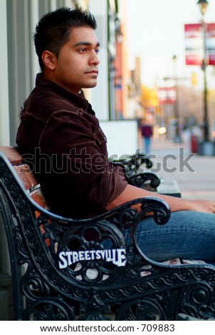 An attractive male sitting on a bench.