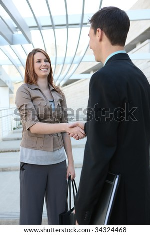An attractive man and woman business team handshake  at the office