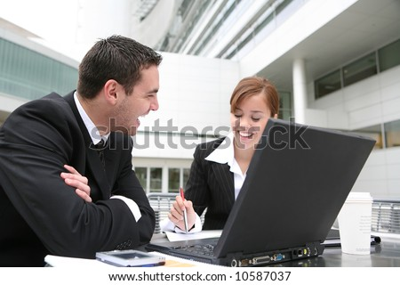 An attractive man and woman business team working on computer - stock photo
