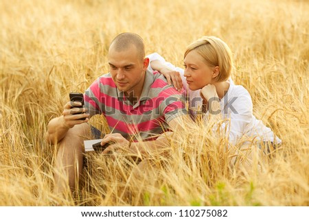 An attractive man and woman couple in the wheat field. Man holding a mobile (cell) phone - stock photo