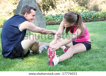 An attractive man and woman couple stretching in the park - stock photo