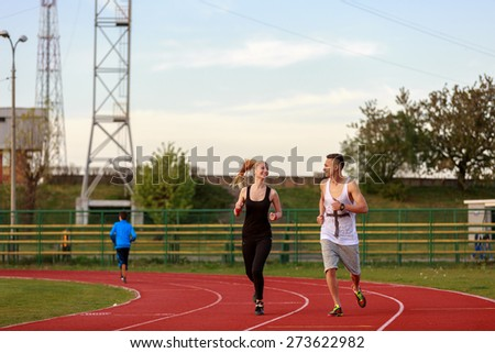 An attractive man and woman jogging on the track - stock photo