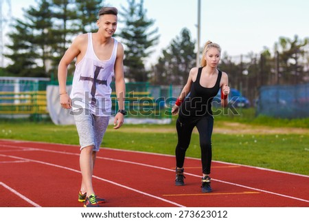 An attractive man and woman jogging on the track