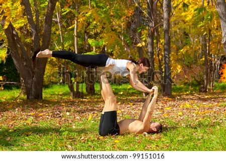 An attractive  man and woman practice tantra yoga in forest - stock photo