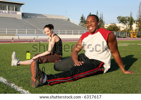 An attractive man and woman stretching before exercise - stock photo