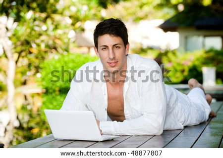 An attractive man lounging by the pool with his laptop outdoors