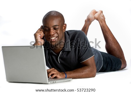 An attractive man using his laptop and talking on his mobile phone against white background