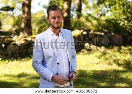 An attractive man wearing a light blue blazer and white shirt, standing outdoors in a green park on a sunny summer day. - stock photo