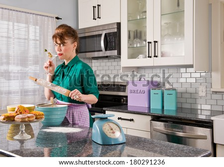 An attractive middle-aged woman in a kitchen wearing a vintage dress, drinking a martini with one hand and a rolling pin in the other with cooking items around her  - stock photo