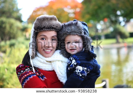 An attractive mother and son in park during the winter season - stock photo