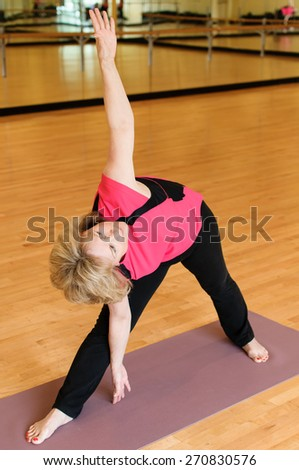 An attractive older woman practices yoga in a studio.  She is in the Extended Triangle Pose  or Trikonasana.  She is bent sideways with one hand touching the ground and the other reaching upwards.   - stock photo
