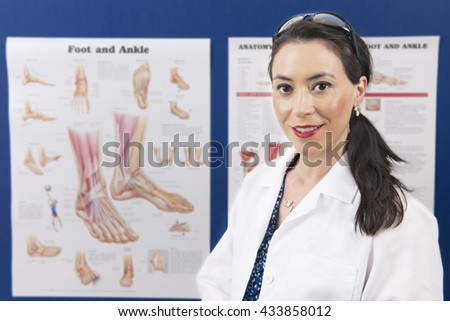 An attractive podiatrist happily looking at the viewer as she stands in front of her education charts.   - stock photo
