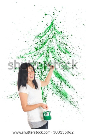 An attractive preteen flinging green paint to create a splattered Christmas tree image behind her.  On a white background. - stock photo