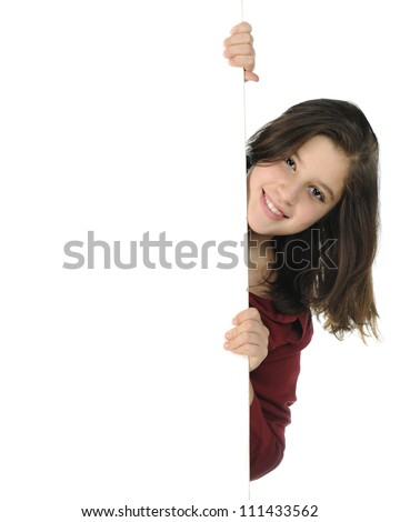 An attractive preteen peeking around a white wall and on a white background. - stock photo