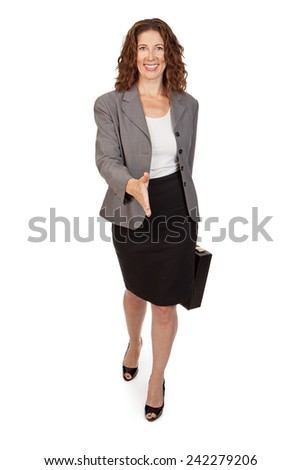 An attractive professional woman holding a briefcase while walking forward with arm extended to shake hands