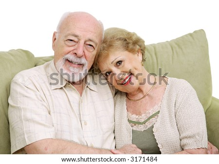 An attractive senior couple at home on the couch together. Isolated on white. - stock photo