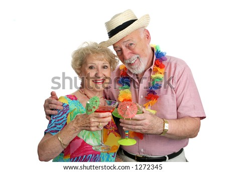An attractive senior couple on vacation drinking tropical drinks with little umbrellas.  Isolated. - stock photo