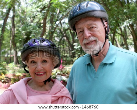 An attractive senior couple wearing bike helmets.
