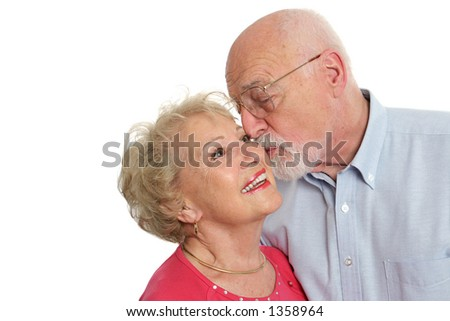 An attractive senior man kissing his beautiful wife on the cheek.  Isolated with room for text. - stock photo