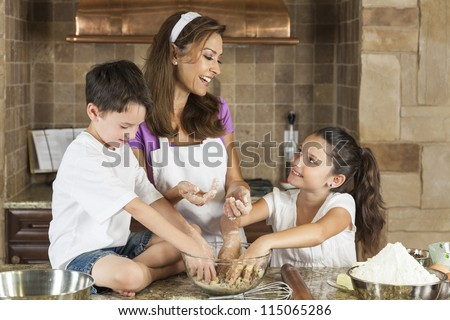 An attractive smiling family of mother, and two children, boy, girl, son, daughter baking and eating fresh chocolate chip cookies in a kitchen at home