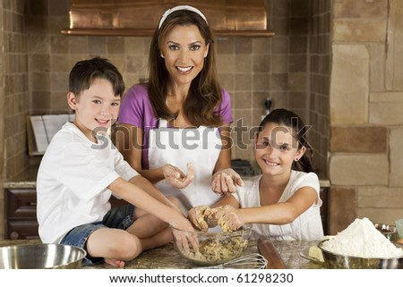 An attractive smiling mother, son and daughter family cooking and baking chocolate chip cookies in a kitchen at home - stock photo