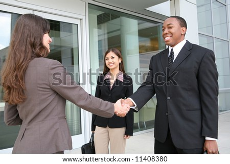 An attractive team of diverse business people shaking hands - stock photo
