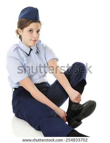 An attractive teen girl in her Jr. ROTC uniform, putting on her shoes.  On a white background. - stock photo