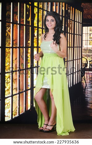 An attractive teen girl looking beautiful in her homecoming dress. - stock photo