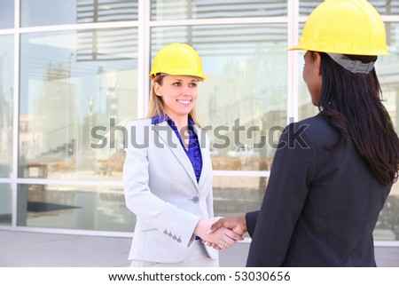 An attractive woman architect team on construction site handshake - stock photo
