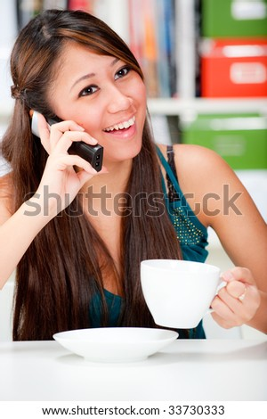 An attractive woman drinking coffee and chatting to her friend on the phone - stock photo