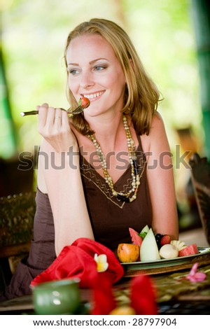 An attractive woman eating a healthy breakfast of fruit - stock photo