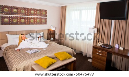An attractive woman in a bathrobe lies on a bed. Watching TV. Horizontal shot. - stock photo