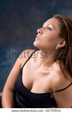 An attractive woman in a sexy low-cut dress looks up into the light. - stock photo