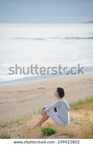 An attractive woman is sitting face to the ocean - stock photo