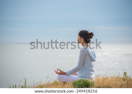 An attractive woman is sitting face to the ocean in lotus position. - stock photo