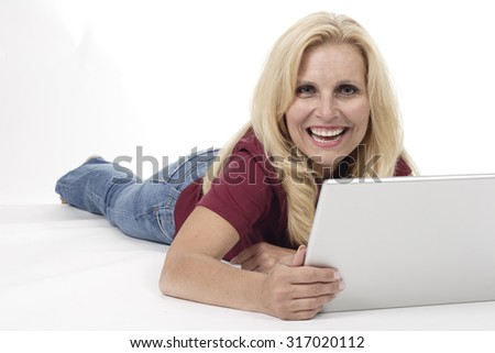 An attractive woman, lying on the floor with a laptop smiling at camera. White background. - stock photo