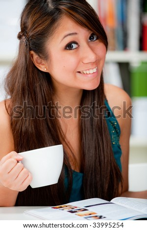 An attractive woman reading her magazine at home with coffee - stock photo