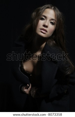 an attractive woman with long brown hair and coat - stock photo