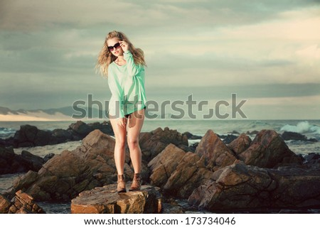 An attractive young blonde lady wearing a green jersey is standing on a rock on the beach where the tide has come in. she is surrounded by water.
