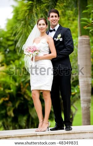 An attractive young bride and groom standing on steps outdoors - stock photo