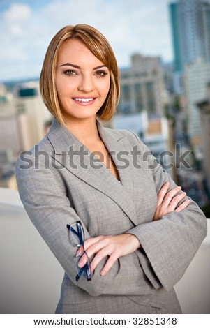 An attractive young business woman in a portrait with city in background.