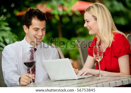 An attractive young businessman and businesswoman having a discussion over wine at an outdoor restaurant - stock photo
