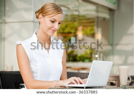 An attractive young businesswoman using her laptop at a cafe