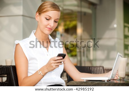 An attractive young businesswoman using her phone and laptop at a cafe - stock photo