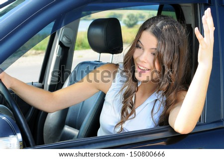 An attractive young Caucasian woman arguing with someone from the front seat of the car - stock photo