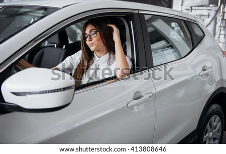 An attractive young Caucasian woman looking at the camera from the front seat of the car