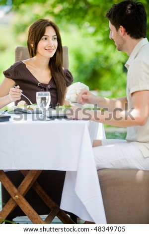 An attractive young couple having a meal outdoors together - stock photo