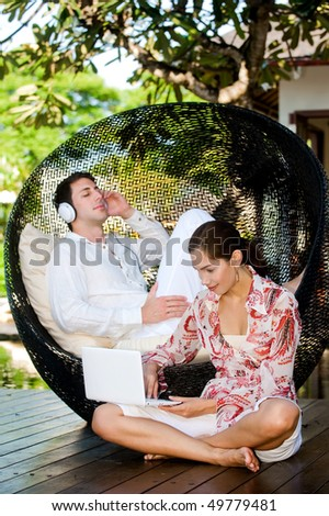 An attractive young couple relaxing outdoors with music and a laptop - stock photo